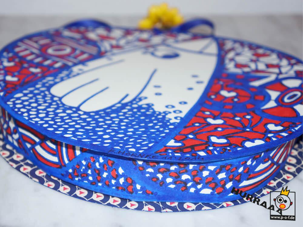 runde Geschenkverpackung mit rotem und blauem Edding bemalt